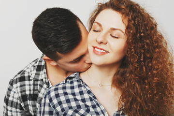 Pleased female keeps eyes shut as recieves passionate kiss in neck from her boyfriend. Young man kisses his young wife, demostrates love. Couple in love have good feelings, being very romantic