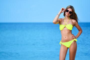 beautiful fit young woman in sexy yellow bikini at the beach