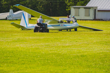 Glider and Tow plane in action on a green airfield