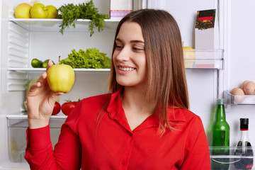 People and healthy nutrition concept. Adorable young woman with cheerful expression, holds green fresh apple, demonstrates her breakfast, dressed in red blouse. Positive woman with delicious fruit