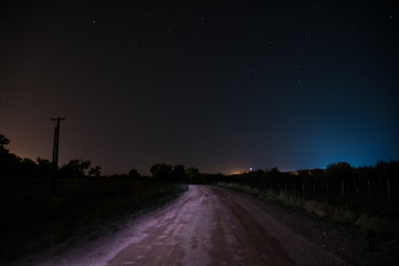 Starry road with blue and red lights in the night sky