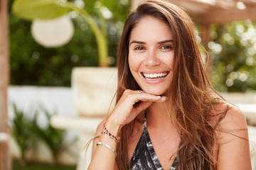 Close up shot of beautiful young brunette female with positve expression, dressed in summer clothing, being in good mood after beauty procedures, sits at outdoor cafeteria. People and emotions