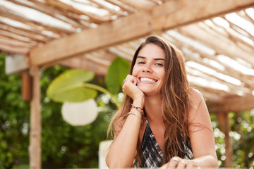 Pleased good looking brunette woman with cheerful smile looks in camera, sits against tropical background in cozy restaurant, enjoys summer hot weather, being in high spirit after spa procedure