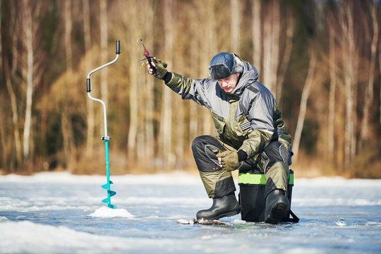 winter fishing on ice. Fisherman hooking fish. Biting
