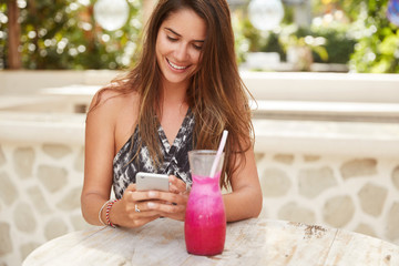 Cheerful gorgeous female lady with luxurious dark hair happy to recieve notification on mobile phone, texts feedback, surrounded with fresh smoothie, enjoys free internet connection in cafe