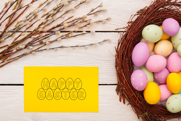 Easter traditional objects isolated on wooden background egss in nest willow and greeting card