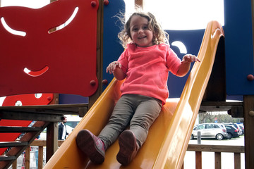 the girl is riding on a children's slide