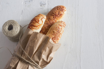 three fresh baked French cheese baguettes in a package