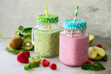 Mason jar mugs with fresh berry cocktails and green smoothies, ingredients for cooking smoothies against a background of gray stone or slate. Healthy vegan food concept.