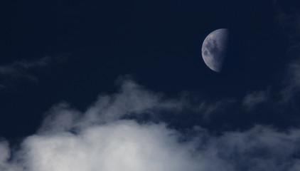 Luna en cuarto menguante se destaca sobre el cielo al atardecer.