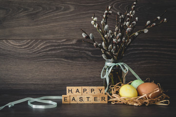 The inscription  happy Easter, made of light wooden cubes, painted eggs in the nest, willow twigs with seals on a dark wooden background