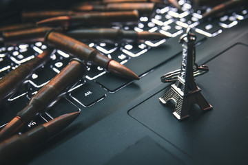 Closeup of laptop computer keyboard, and gun bullets, representing the concept of cyber attacks, Journalism, terrorism, support for terrorists, Eiffel Tower, Paris