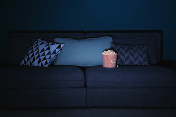 Comfortable couch with popcorn indoors. Home cinema