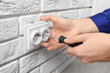 Electrician repairing socket on brick wall