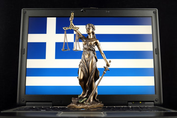 Symbol of law and justice with Greece Flag on laptop. Studio shot.