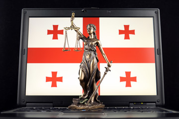 Symbol of law and justice with Georgia Flag on laptop. Studio shot.