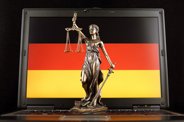 Symbol of law and justice with Germany Flag on laptop. Studio shot.