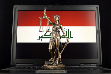 Symbol of law and justice with Iraq Flag on laptop. Studio shot.
