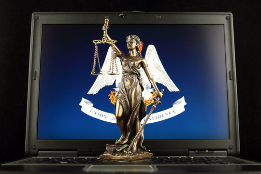 Symbol of law and justice with Louisiana State Flag on laptop. Studio shot.