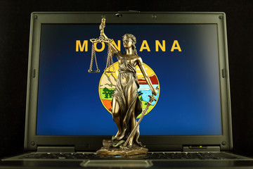 Symbol of law and justice with Montana State Flag on laptop. Studio shot.