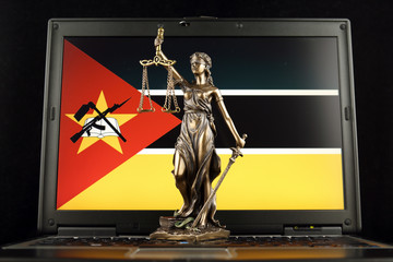 Symbol of law and justice with Mozambique Flag on laptop. Studio shot.