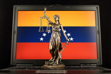 Symbol of law and justice with Venezuela Flag on laptop. Studio shot.