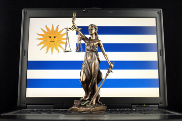 Symbol of law and justice with Uruguay Flag on laptop. Studio shot.