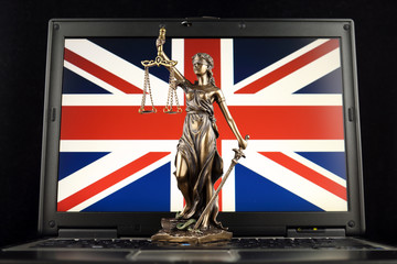 Symbol of law and justice with United Kingdom Flag on laptop. Studio shot.
