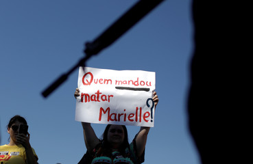 """A demonstrator holds a banner which reads """"Who ordered to kill Marielle?"""" as she walks past a police officer during a rally against the shooting of Rio de Janeiro city councilor Marielle Franco, in Rio de Janeiro"""