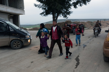 Kurdish girl reacts as she walks with her family in Afrin