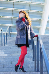 Sexy woman in a black dress, red tights and a fur coat standing on the stairs