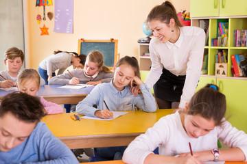 Teacher woman helping children during lesson in schoolroom