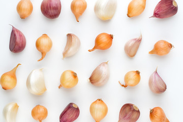 Onion and garlic isolated on white background, top view. Wallpaper abstract composition of vegetables.