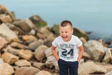 little boy laughing on the beach and standing on rocks near sea. Positive human emotions