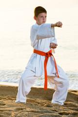 Boy practising karate at seaside