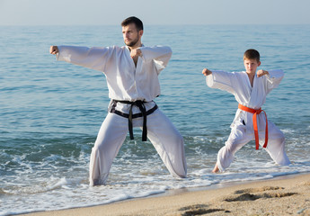 man and teenager show karate poses
