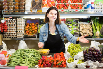 Female shopping assistant demonstrating assortment of grocery shop
