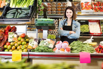 shopping assistant weighing fruit and vegetables in grocery shop