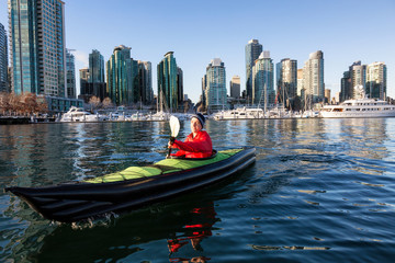 Wall Mural - Man on an inflatable kayak is kayaking in Coal Harbour during a sunny morning. Taken in Downtown Vancouver, British Columbia, Canada.
