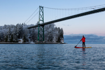 Fotomurales - Adventurous man on a Standup Paddle Board is padding near Lions Gate Bridge during a vibrant winter sunrise. Taken in Vancouver, British Columbia, Canada.