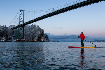 Wall Mural - Adventurous man on a Standup Paddle Board is padding near Lions Gate Bridge during a vibrant winter sunrise. Taken in Vancouver, British Columbia, Canada.