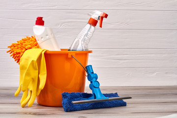 Cleaning supplies in colorful bucket. Cleaning spray, gloves and brush on wooden background. Make your home cleaner for spring.