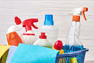 Assortment of detergents in laundry basket. Close up variety of bottles with cleaning liquid. Hacks and tips for clean up your home.