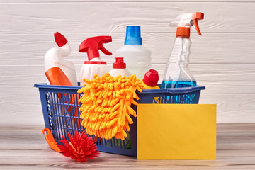House cleaning products in basket. Bottles with cleaning liquid, brush, microfiber glove and blank paper card. House cleaning service.