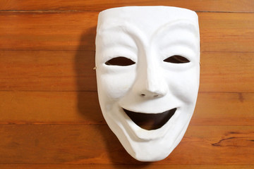 White happy human face expression mask with on a wooden table