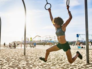 athletic african american woman swinging between gymnastic rings at beach exercise park