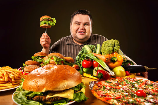 Diet fat man who makes choice between healthy and unhealthy food. Overweight male with hamburgers, french fries. Health problems due to malnutrition.