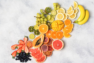 Wall Mural - Above view of healthy fruits in rainbow colours, strawberries, mango, grapes, bananas, grapefruit on the off white table, copy space for text, selective focus