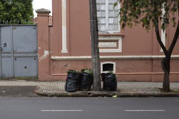 Lixo em sanitos largados na calçada
