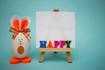 Happy text from colorful wooden letters on easel with funny eggs in form of cute bunny on blue background. Happy easter. Festive decoration